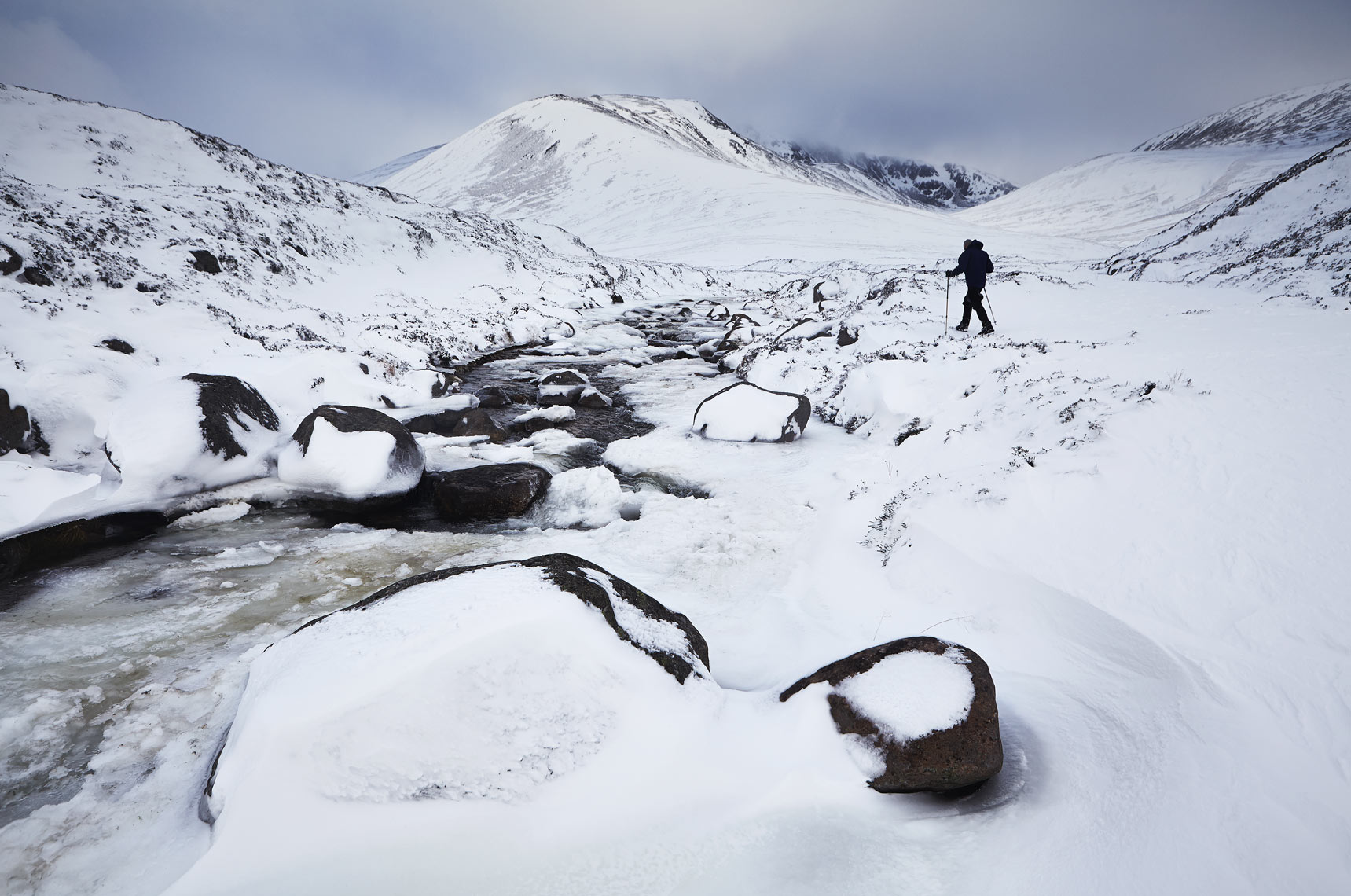 Lone hiker by frozen stream